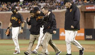 San Francisco Giants pitcher Tim Lincecum, center, walks off the field with trainers, center fielder Angel Pagan, left, and manager Bruce Bochy, right, after being struck by a ball hit by Oakland Athletics' Daric Barton during the fourth inning of a spring exhibition baseball game in San Francisco, Friday, March 28, 2014. (AP Photo/Jeff Chiu)