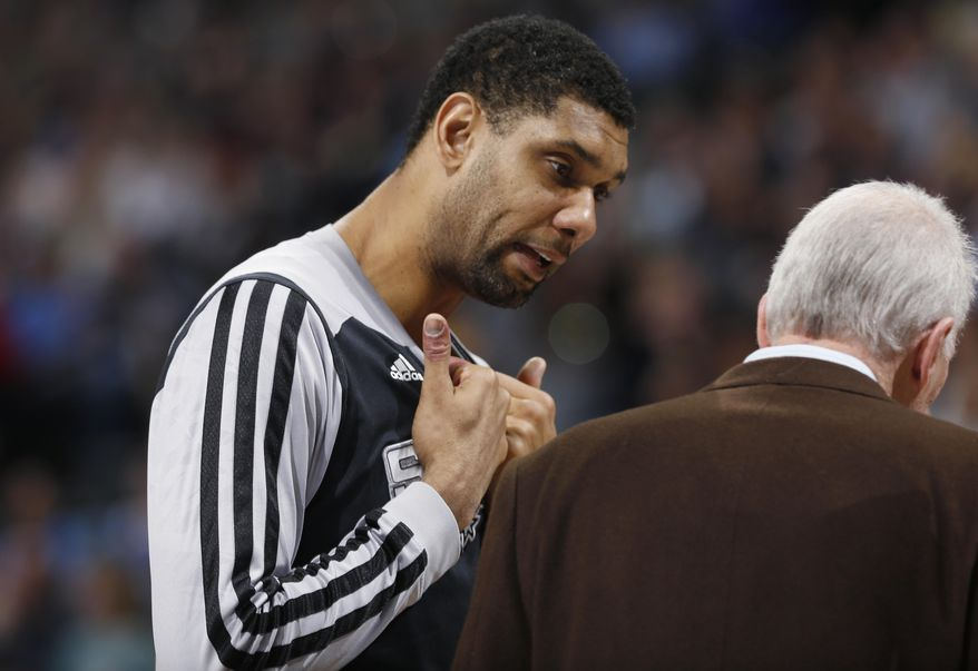 San Antonio Spurs center Tim Duncan, left, confers with coach Gregg Popovich during a timeout against the Denver Nuggets in the fourth quarter of the Spurs' 133-102 victory in an NBA basketball game in Denver on Friday, March 28, 2014. (AP Photo/David Zalubowski)