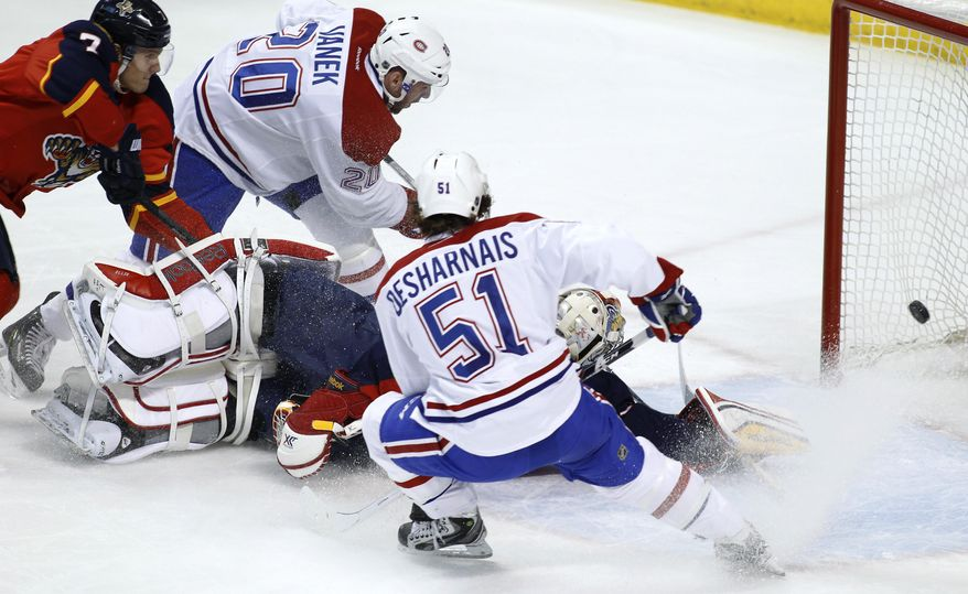 Montreal Canadiens left wing Thomas Vanek (20) scores a goal as Florida Panthers' Dmitry Kulikov (7) defends during the first period of an NHL hockey game in Sunrise, Fla., on Saturday, March 29, 2014. (AP Photo/Terry Renna)