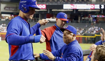 Chicago Cubs' Anthony Rizzo, left, gets high-fives from manager Rick Renteria, right, and bench coach Brandon Hyde after Rizzo scored a run against the Arizona Diamondbacks in the fourth inning of a spring training baseball game, Friday, March 28, 2014, in Phoenix. (AP Photo/Ross D. Franklin)
