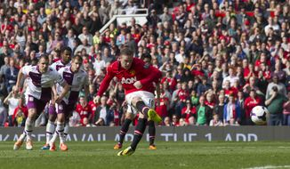Manchester United's Wayne Rooney scores a penalty against Aston Villa, during their English Premier League soccer match at Old Trafford Stadium, Manchester, England, Saturday March 29, 2014. (AP Photo/Jon Super)