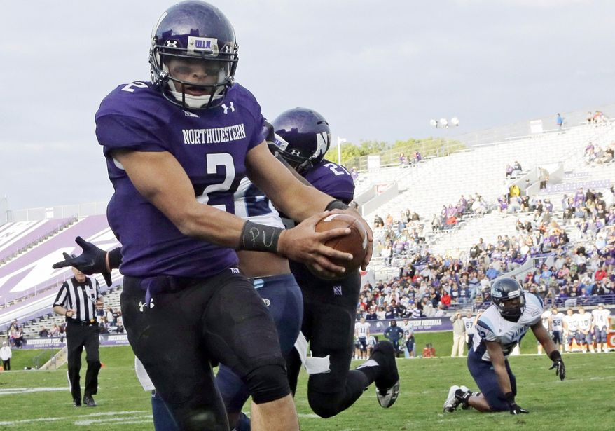 "FILE - In this Sept. 21, 2013, file photo, Northwestern quarterback Kain Colter (2), wears APU for ""All Players United"" on wrist tape as he scores a touchdown during an NCAA college football game against Maine in Evanston, Ill. The five-member regulatory board that will ultimately decide if Northwestern University football players can unionize has itself been in the middle of a firestorm. The very makeup of the National Labor Relations Board has been challenged in a case now before the Supreme Court. And Republicans contend the agency has being overly friendly to organized labor.  (AP Photo/Nam Y. Huh, File)"