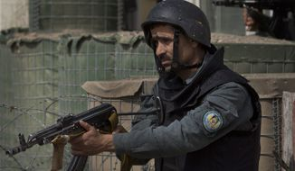 Afghan police men take up positions as Taliban militants attacked the main Afghan election commission's headquarters in the outskirts of Kabul, Afghanistan, firing on the compound with rocket-propelled grenades and heavy machine guns from a house outside its perimeter wall, Saturday, March 29, 2014. Dozens of employees and other people who had been inside the Independent Election Commission compound took cover in the basement, and no casualties were reported. But two warehouses were hit and set on fire, witnesses said. (AP Photo/Anja Niedringhaus)