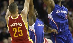 Houston Rockets forward Chandler Parsons (25) takes a shot over Los Angeles Clippers' DeAndre Jordan (6) and Reggie Bullock during the second quarter of an NBA basketball game, Saturday, March 29, 2013, in Houston. (AP Photo/Patric Schneider)