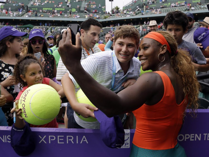 """Serena Williams, right, takes a """"selfie"""" photo with a fan following her 7-5, 6-1 victory over Li Na, of China, during the women's final at the Sony Open Tennis tournament, Saturday, March 29, 2014, in Key Biscayne, Fla. (AP Photo/Alan Diaz)"""