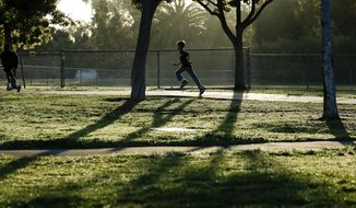 ** FILE ** In this March 14, 2014, picture, students take part in an early morning running program at an elementary school in Chula Vista, Calif. (AP Photo/Gregory Bull)