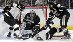 Providence goaltender Jon Gillies makes a save as Steven Shamanski (28) and Union's Daniel Ciampini, left, and Daniel Carr fight for the puck during the first period of the final of the men's NCAA East Regional college hockey tournament, Saturday, March 29, 2014, in Bridgeport, Conn. (AP Photo/Fred Beckham)