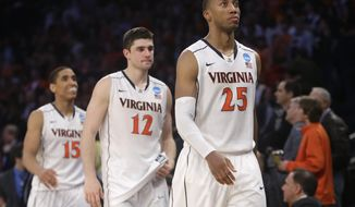 Virginia players, right to left, Akil Mitchell, Joe Harris, and Malcolm Brogdon leave the court after losing to Michigan State 61-59 in a regional semifinal at the NCAA men's college basketball tournament, early Saturday, March 29, 2014, in New York. (AP Photo/Frank Franklin II)