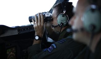 Wing Commander Rob Shearer looks through binoculars on the flight deck of a Royal New Zealand Air Force P-3K2 Orion aircraft searching for missing Malaysian Airlines flight 370 over the southern Indian Ocean, March 29, 2014. A day after the search for the Malaysian jetliner shifted to a new area of the Indian Ocean, ships on Saturday plucked objects from the sea to determine whether they were related to the missing jet. None were confirmed to be from the plane, leaving searchers with no sign of the jet three weeks after it disappeared. (AP Photo/Jason Reed, Pool)