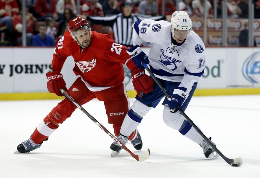 Tampa Bay Lightning's Ondrej Palat (18), of the Czech Republic, takes a shot on goal against the defense of Detroit Red Wings' Drew Miller (20) during the first period of an NHL hockey game, Sunday, March 30, 2014, in Detroit. (AP Photo/Duane Burleson)