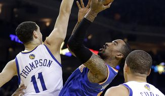 New York Knicks' J.R. Smith, center, shoots against Golden State Warriors' Klay Thompson (11) during the first half of an NBA basketball game, Sunday, March 30, 2014, in Oakland, Calif. (AP Photo/Ben Margot)