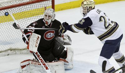 Notre Dame left wing Mario Lucia, right, chases a rebound in front of St. Cloud State goalie Ryan Faragher (29) during the first period of an NCAA West college regional hockey game in St. Paul, Minn., Saturday, March 29, 2014. (AP Photo/Ann Heisenfelt)