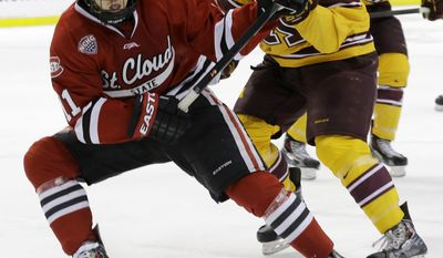 St. Cloud State forward Kalle Kossila, left, and Minnesota defenseman Jake Parenteau (6) chase the puck during the second period of an NCAA West college regional hockey game in St. Paul, Minn., Sunday, March 30, 2014.  (AP Photo/Ann Heisenfelt)