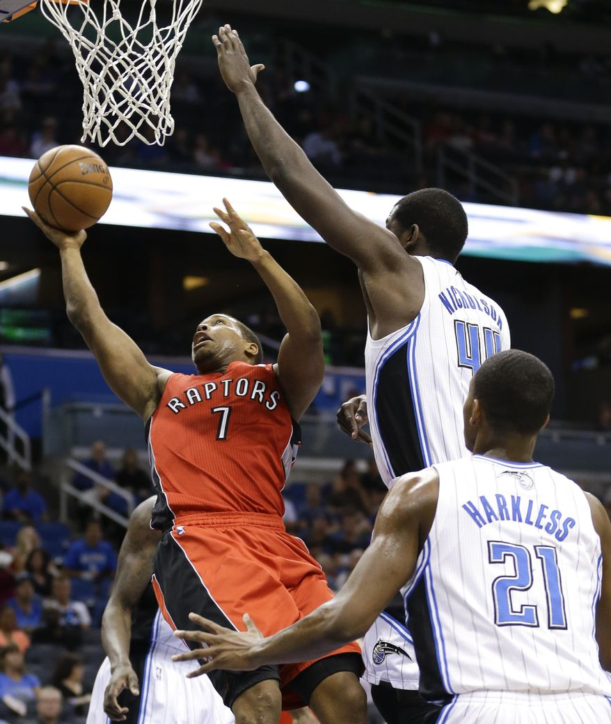Toronto Raptors guard Kyle Lowry (7) gets off a shot past Orlando Magic's Andrew Nicholson (44) and Maurice Harkless (21) during the first half of an NBA basketball game in Orlando, Fla., Sunday, March 30, 2014. (AP Photo/John Raoux)