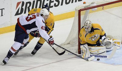 Washington Capitals right wing Tom Wilson (43) has his shot block by Nashville Predators goalie Carter Hutton (30) as defenseman Michael Del Zotto (5) defends in the first period of an NHL hockey game on Sunday, March 30, 2014, in Nashville, Tenn.  (AP Photo/Mark Zaleski)