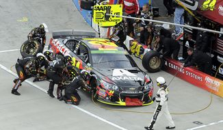 Jeff Gordon make a pit stop during a NASCAR Sprint Cup Series auto race at Martinsville Speedway in Martinsville, Va., Sunday, March 30, 2014. (AP Photo/Mike McCarn)