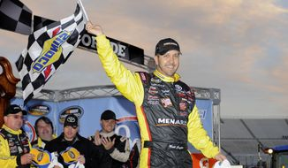 Driver Matt Crafton celebrates in victory lane after winning a NASCAR Truck Series auto race at Martinsville Speedway in Martinsville, Va., Sunday, March 30, 2014. (AP Photo/Mike McCarn)