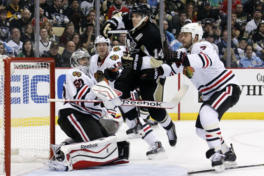 Pittsburgh Penguins' Chris Kunitz (14) leaps across the goal crease between Chicago Blackhawks goalie Corey Crawford (50) and Brent Seabrook (7) in the second period of an NHL hockey game in Pittsburgh, Sunday, March 30, 2014. (AP Photo/Gene J. Puskar)