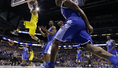Michigan's Jordan Morgan dunks during the second half of an NCAA Midwest Regional final college basketball tournament game against Kentucky Sunday, March 30, 2014, in Indianapolis. (AP Photo/Michael Conroy)