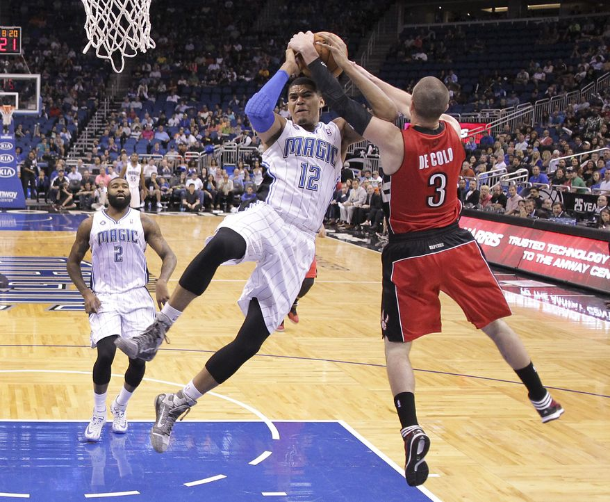Toronto Raptors guard Nando de Colo (3) fouls Orlando Magic's Tobias Harris (12) as he tries to block a shot during the first half of an NBA basketball game in Orlando, Fla., Sunday, March 30, 2014. (AP Photo/John Raoux)