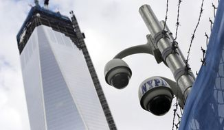 FILE - In this Feb. 25, 2013, file photo, New York Police Department security cameras are in place at the National Sept. 11 Memorial and Museum in New York. One World Trade Center is on the left. Sen. Charles Schumer stood by the World Trade Center on Sunday, March 30, 2014, demanding that federal officials review security after daredevils twice sneaked to the top of the site's signature, 104-story skyscraper. (AP Photo/Mark Lennihan, File)
