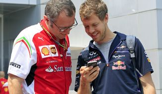 Ferrari Formula One team principal Stefano Domenicali, left, and Red Bull Racing driver Sebastian Vettel of Germany look at a smartphone before the Malaysian Formula One Grand Prix at Sepang International Circuit in Sepang, Malaysia, Sunday, March 30, 2014. (AP Photo/Peter Lim)