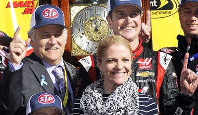 Clay Campbell, left, president of Martinsville Speedway celebrates in victory lane with race winner Kurt Busch, right, Patricia Driscoll, Busch's girlfriend and her son, Houston after a NASCAR Sprint Cup auto race at Martinsville, Speedway in Martinsville, VA., Sunday March 30, 2014. (AP Photo/Mike McCarn)