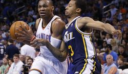 Oklahoma City Thunder guard Russell Westbrook, left, drives past Utah Jazz guard Trey Burke (3) in the second quarter of an NBA basketball game in Oklahoma City, Sunday, March 30, 2014. (AP Photo/Sue Ogrocki)