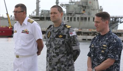 U.S. Navy captain Mark Matthews, right, Royal Australian Navy commodore Peter Leavy, center, and chief of the navy Vice Admiral Ray Griggs stand on the dock before a press conference at naval base HMAS Stirling about the defense ship Ocean Shield and her roll in the search for missing Malaysia Airlines Flight MH370 in Perth, Australia, Sunday, March 30, 2014.(AP Photo/Rob Griffith)