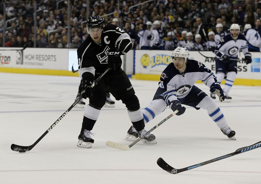 Los Angeles Kings right wing Dustin Brown (23) looks to pass the puck as he pressured by Winnipeg Jets center Jim Slater (19) during the second period of an NHL hockey game at the Staples Center Saturday, March 29, 2014, in Los Angeles. (AP Photo/Kevork Djansezian)