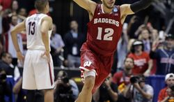 Wisconsin 's Traevon Jackson celebrates in front of Arizona's Nick Johnson (13) as time runs out in overtime of a regional final NCAA college basketball tournament game, Saturday, March 29, 2014, in Anaheim, Calif. Wisconsin won 64-63 in overtime. (AP Photo/Alex Gallardo)