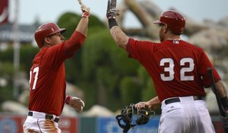 Los Angeles Angels' Mike Trout, left, celebrates with Josh Hamilton, right, after scoring on a hit by Albert Pujols during the first inning of an exhibition baseball game against the Los Angeles Dodgers in Anaheim, Calif., Saturday, March 29, 2014. (AP Photo/Kelvin Kuo)