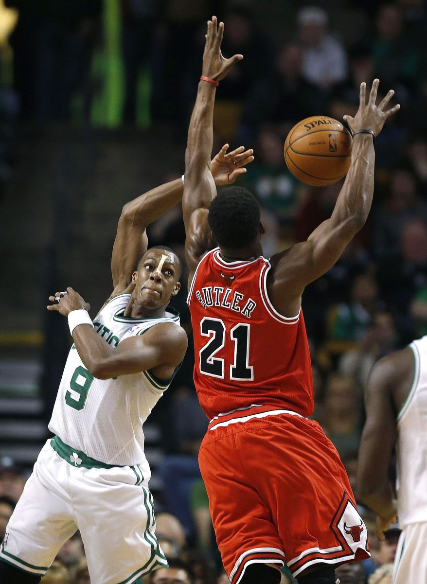 Boston Celtics' Rajon Rondo (9) passes in front of Chicago Bulls' Jimmy Butler (21) in the first quarter of an NBA basketball game in Boston, Sunday, March 30, 2014. (AP Photo/Michael Dwyer)