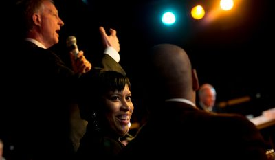 Councilmember Muriel Bowser (D-Ward 4), center and musician and promoter Carlos Allen, right, speak together as Washington, D.C. Councilmember Jack Evans (D-Ward 2), left, speaks at a mayoral debate hosted by the Washington City Paper at the Black Cat on 14th Street in Northwest, Washington, D.C., Sunday, March 16, 2014. (Andrew Harnik/The Washington Times)