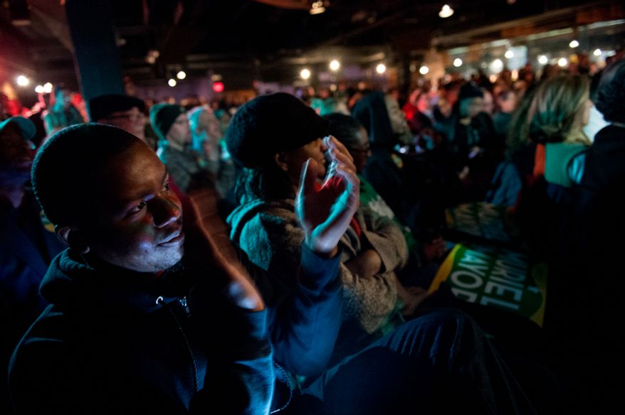 Anthony Lorenzo Green, left, applauds as he and other district residents listen to candidates for mayor of Washington, D.C. as they speak at a debate hosted by the Washington City Paper at the Black Cat on 14th St. in Northwest, Washington, D.C., Sunday, March 16, 2014. (Andrew Harnik/The Washington Times)