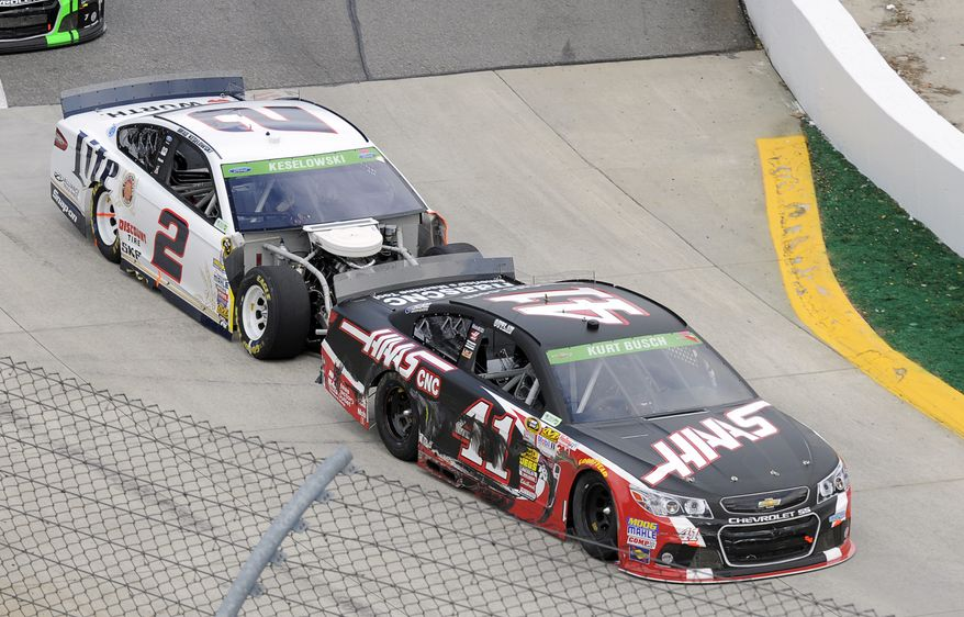 Brad Keselowski (2) bumps Kurt Busch (41) as they enter Turn 1 during a NASCAR Sprint Cup auto race at Martinsville, Speedway, Sunday, March 30, 2014, in Martinsville, Va. The two drivers were involved in a pit road accident earlier in the race. (AP Photo/Mike McCarn)