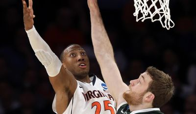 Virginia forward Akil Mitchell, left, goes up for a shot against Michigan State forward Matt Costello during the first half in a regional semifinal of the NCAA men's college basketball tournament, Friday, March 28, 2014, in New York. (AP Photo/Seth Wenig)
