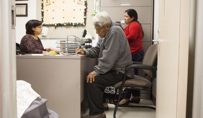 Juana Lopez, right, and her husband Alberto Lopez, center, get help buying health insurance at a service center, Monday March 31, 2014, in Houston. Monday is the deadline to sign up for private heath insurance in the online markets created by President Obama's heath care law. (AP Photo/Michael Stravato)