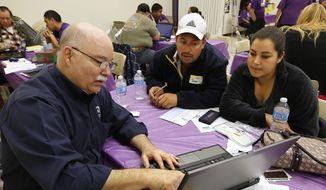 ** FILE ** Michael Wilson, left, a certified Cover California insurance agent, explains a health insurance plan to Jose Gomez and his wife, Laura, at a registration site hosted by Service Employees International Union-United Healthcare Workers, Monday, March 31, 2014, in Sacramento, Calif. (AP Photo/Rich Pedroncelli)