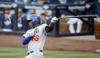 Los Angeles Dodgers' Yasiel Puig breaks his bat as he grounds out while playing the San Diego Padres during the third inning of an opening night baseball game on Sunday, March 30, 2014, in San Diego. (AP Photo/Gregory Bull)