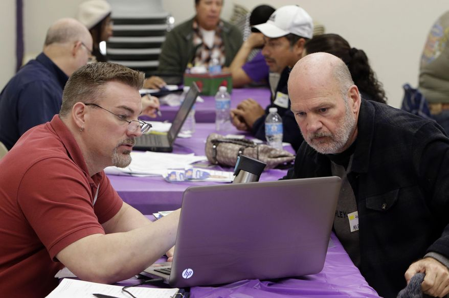 Keith Saunders, left, a certified Cover California insurance agent, explains a health insurance plan to Mark Tammes at a registration site hosted by Service Employees International Union-United Healthcare Workers, Monday, March 31, 2014, in Sacramento, Calif. (AP Photo/Rich Pedroncelli) ** FILE **
