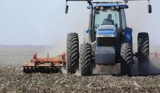 FILE - In this April 4, 2013 file photo a central Illinois corn and soybean farmer cultivates his field for spring planting in Waverly, Ill. The U.S. Department of Agriculture says in its annual forecast released Monday, March 31, 2014 the number of acres devoted to corn is expected to shrink about 4 percent this year as farmers devote more of their land to soybeans. (AP Photo/Seth Perlman, File)