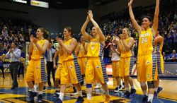 South Dakota State head coach Aaron Johnston, far left, celebrates and thanks the home crowd for their support at the end of an NCAA college basketball game in the quarterfinals of the WNIT, Sunday, March 30, 2014, in Brookings, S.D. South Dakota State defeated Indiana 76-64. (AP Photo/Eric Landwehr)