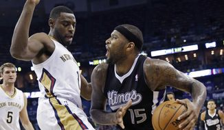 Sacramento Kings center DeMarcus Cousins (15) drives to the basket against New Orleans Pelicans forward Tyreke Evans (1) in the first half of an NBA basketball game in New Orleans, Monday, March 31, 2014. (AP Photo/Gerald Herbert)