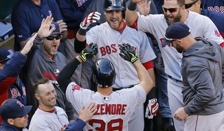 Teammates greet Boston Red Sox' Grady Sizemore (38) in the dugout after he hit a solo home run in the fourth inning of an opening day baseball game against the Baltimore Orioles, Monday, March 31, 2014, in Baltimore. (AP Photo/Patrick Semansky)
