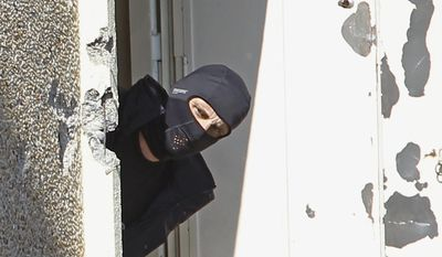 FILE -  In this March 23, 2014 file photo, a masked police officer searches for clues at  terrorist Mohamed Merah's apartment building in Toulouse, southern France. To stop the stream of French youths pursuing jihad in Syria, France is preparing to do something it has never done before: Tackle terrorism at its roots before it starts, by involving schools, parents and local Muslim leaders, The Associated Press has learned. Memories are still fresh of the radical Islamic Frenchman Merah who gunned down children at a Toulouse Jewish school in 2012, after training in Afghanistan and Pakistan. (AP Photo/Remy de la Mauviniere)