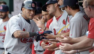 St. Louis Cardinals' Yadier Molina, left, is congratulated in the dugout after hitting a solo home run off Cincinnati Reds starting pitcher Johnny Cueto in the seventh inning of a baseball game, Monday, March 31, 2014, on opening day in Cincinnati. (AP Photo/Michael Keating)