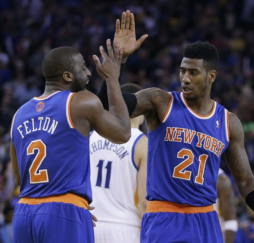 New York Knicks' Raymond Felton, left, celebrates with Iman Shumpert (21) in the final seconds of an NBA basketball game against the Golden State Warriors Sunday, March 30, 2014, in Oakland, Calif. (AP Photo/Ben Margot)