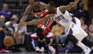 Washington Wizards' Trevor Booker (35) and Charlotte Bobcats' Kemba Walker (15) during the first half of an NBA basketball game in Charlotte, N.C., Monday, March 31, 2014. (AP Photo/Chuck Burton)
