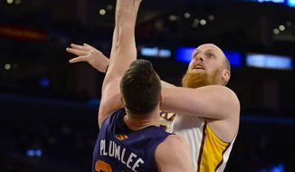 Los Angeles Lakers center Chris Kaman. back right, drives on Phoenix Suns center Miles Plumlee (22) for a basket in the first half of an NBA basketball game, Sunday, March 30, 2014, in Los Angeles.(AP Photo/Gus Ruelas)